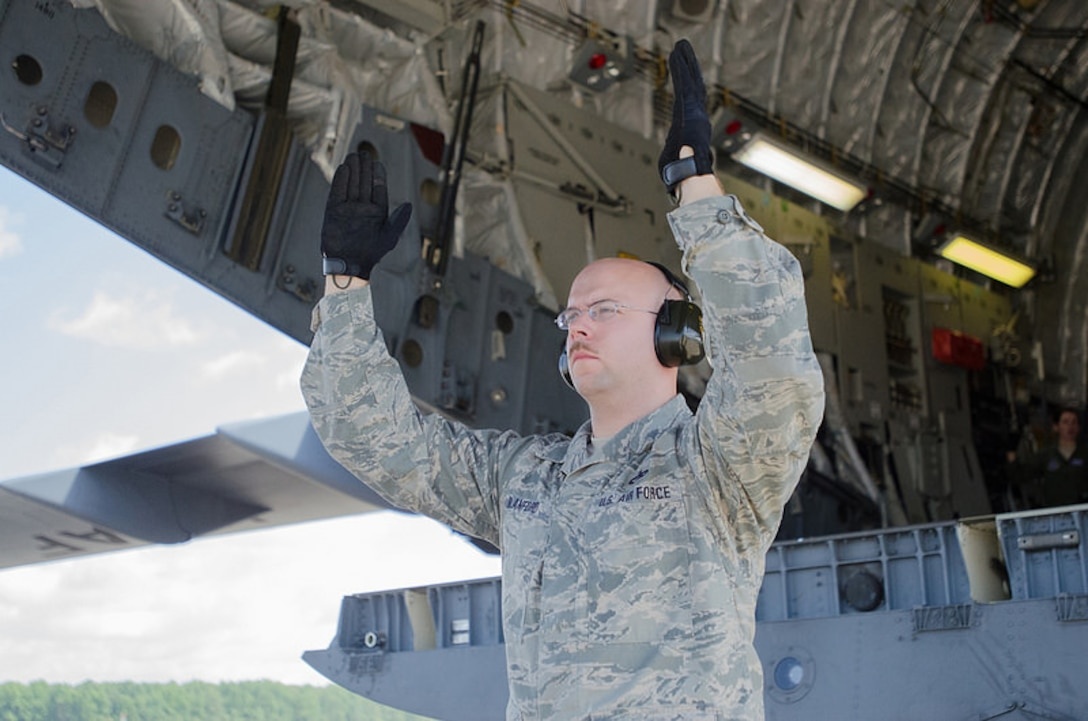 Tech. Sgt. Jerrod Blanford, an aerial porter from the Kentucky Air National Guard's 123rd Contingency Response Group, spots a forklift as it unloads cargo from a Kentucky Air Guard C-130 Hercules during Capstone '14, a homeland earthquake-response exercise at Fort Campbell, Ky., on June 17, 2014. The 123rd CRG is joining with the U.S. Army's 688th Rapid Port Opening Element to operate a Joint Task Force-Port Opening here from June 16 to 19, 2014. (U.S. Air National Guard photo by Master Sgt. Phil Speck)