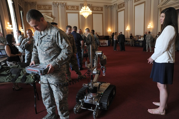 Senior Airman Brian Mink shows how he does not have to watch while using an explosive ordnance disposal Air Force Medium Size Robot to lift a bottle of water off the floor during EOD Day on the Hill June 11, 2014, in Washington, D.C. EOD Day on the Hill is an annual event hosted by the Congressional EOD Caucus. The House EOD Caucus informs congressional members and staff about how EOD protects the nation's interests and citizens at home and abroad. Mink is an 11th Civil Engineer Squadron EOD technician assigned to Joint Base Andrews, Md. (U.S. Air Force photo/Master Sgt. Tammie Moore)