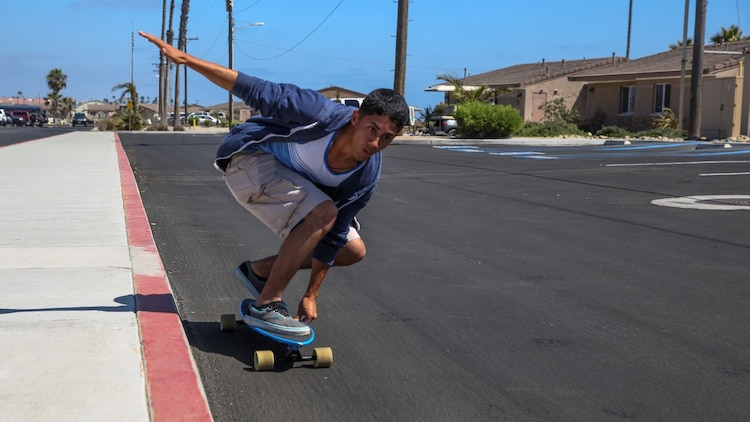 Sergeant Richard Hernandez, cyber network technician, 15th Marine Expeditionary Unit, rides his longboard aboard Camp Pendleton, Calif., June 13, 2014. Hernandez, 22, is from Temecula, Calif. (U.S. Marine Corps photo by Lance Cpl. Anna Albrecht/Released)