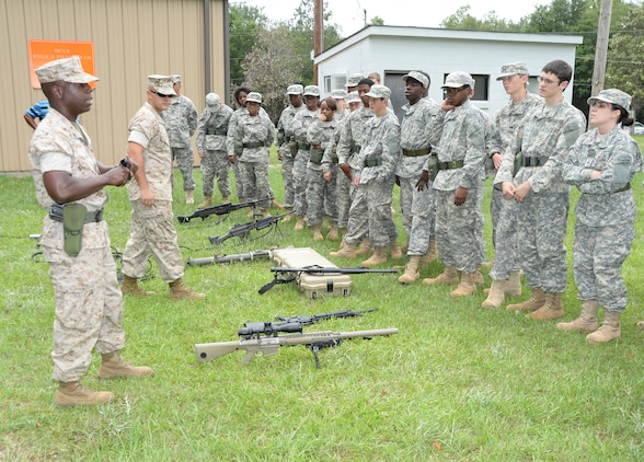 Sgt. Emal Britt, armory maintenance chief, Logistical Support Division (far left) and Sgt. Joshua M. Loflin, career planner, at Marine Corps Logistics Base Albany, identify the series type and use of several weapons to Army Junior Reserve Officers Training Corps cadets from Americus-Sumter High School, Americus, Ga., who attended a leadership training camp on the installation, June 3.