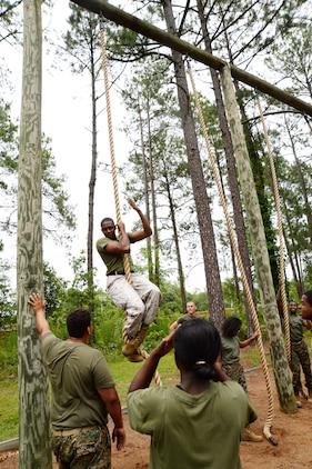Marine Junior Reserve Officers Training Corps cadets from Dougherty Comprehensive High School, Albany, Ga., watch as Sgt. Marcus Keyes, training noncommissioned officer, Operations and Training Division, Marine Corps Logistics Base Albany, demonstrates the proper technique for mastering the rope climb. The training was completed as part of a leadership camp, June 3.