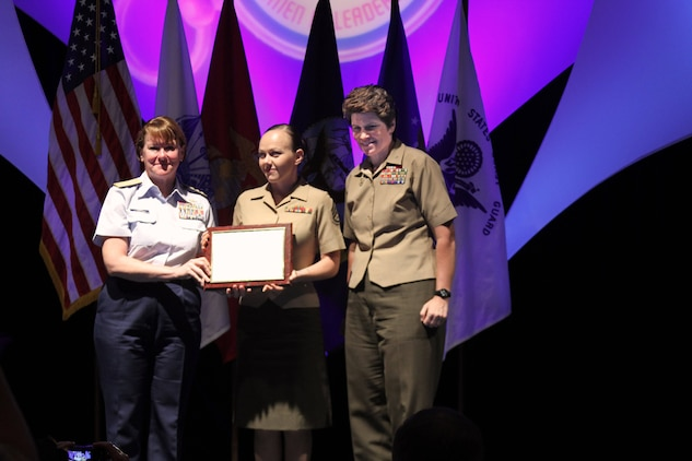 U.S Marine Corps Staff Sgt. Melissa Johnson, center, Marine Corps Air Station Beaufort's operations chief, receives the Major Megan McClung Leadership Award from U.S Marine Corps Brig. Gen. Lori Reynolds, commanding general of Marine Corps Recruit Depot Parris Island and the Eastern Recruiting Region, at the Joint Leadership Symposium, June 12, 2014. The award is named after U.S. Marine Corps Major Megan McClung, who became the first female officer to be killed in the War in Iraq in 2006. Johnson earned the award for her outstanding service as drill instructor, senior drill instructor and chief drill instructor with P Company, 4th Recruit Training Battalion, aboard Marine Corps Recruit Depot Parris Island, South Carolina.(U.S. Marine Corps photo by Cpl. Aaron Diamant/Released)