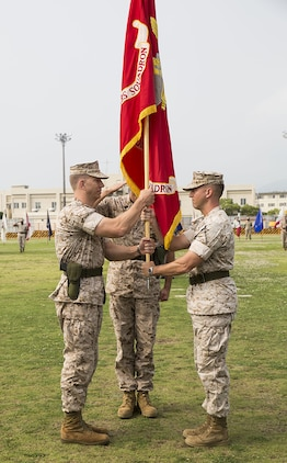 Lt. Col. F. Lance Lewis, right, passes the Headquarters and Headquarters Squadron colors to Lt. Col. Karl Schmidt during a change-of-command ceremony on the parade deck, June 9, 2014, aboard Marine Corps Air Station Iwakuni, Japan. Schmidt came to H&HS from U.S. Central Command aboard MacDill Air Force Base, Tampa, Fla.