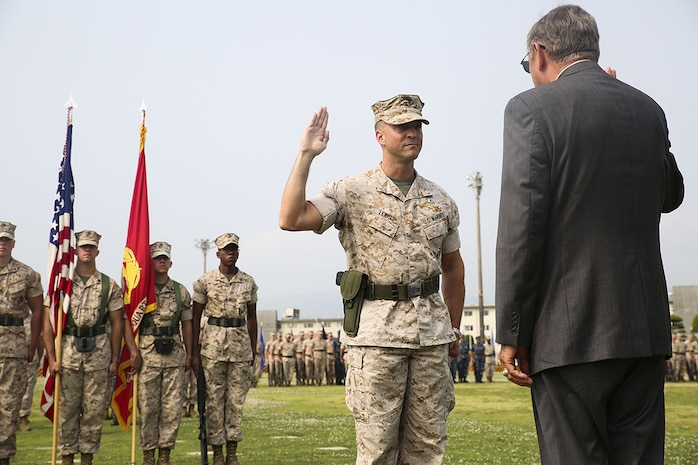 Lt. Col. F. Lance Lewis reaffirms his oath of enlistment during a change-of-command ceremony on the parade deck, June 9, 2014, aboard Marine Corps Air Station Iwakuni, Japan. Lewis's father, Retired Rear Adm. Frederick L. Lewis, conducted the reaffirmation.