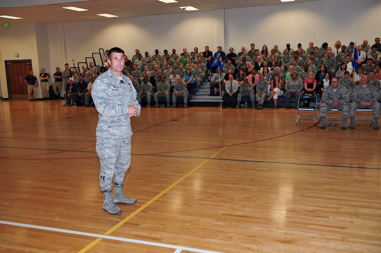 Col. John Wagner, 460th Space Wing commander, left, speaks to the men and women of Team Buckley where he presented his expectations and goals for his coming term June 18, 2014, at the fitness center on Buckley Air Force Base, Colo. Wagner assumed command of the 460th SW after serving in several space-based positions across the Air Force. (U.S. Air Force photo by Senior Airman Phillip Houk/Released)