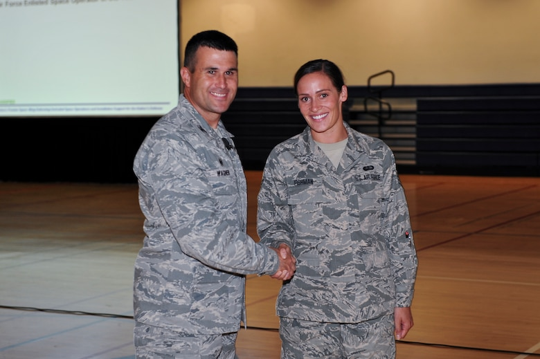 Col. John Wagner, 460th Space Wing commander, left, congratulates Staff Sgt. Diana Fishman, Mile High Honor Guard assistant flight chief, for winning the Chief Master Sergeant of the Air Force Base Honor Guard Member of the Year Award June 18, 2014, at the fitness center on Buckley Air Force Base, Colo. This Air Force level award recognized a base-level honor guard member for their significant contributions in the area of military honors and ceremonies. (U.S. Air Force photo by Senior Airman Phillip Houk/Released)