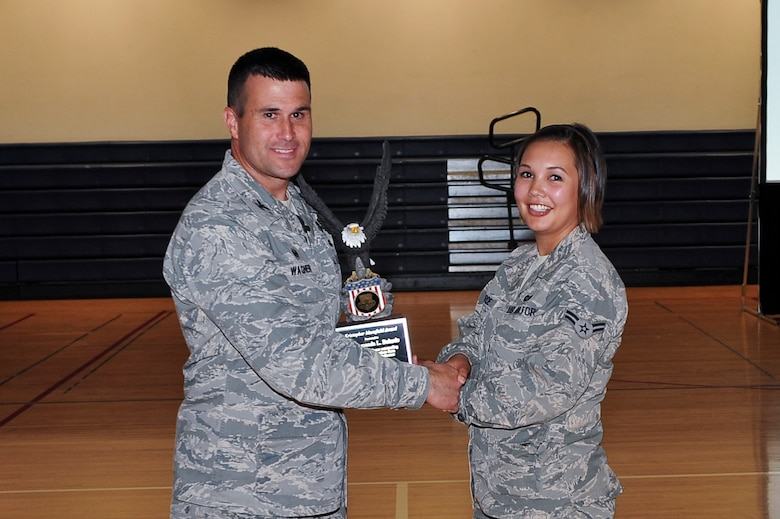 Col. John Wagner, 460th Space Wing commander, left, presents the Kristopher Mansfield Award to,  Airman 1st Class Amanda Belarde, 460th SW military justice paralegal, at the 460th SW commanders call June 18, 2014, at the fitness center on Buckley Air Force Base, Colo. The Mansfield Award is presented each year to an Airman who dedicates themselves to the reduction of alcohol-related incidents in their community. (U.S. Air Force photo by Senior Airman Phillip Houk/Released)