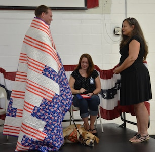 Anne Mixon from Quilts of Valor (right), presents retired U.S. Marine Sgt. Kyle Miller, a quilt in recognition of his military service while Miller's wife Vanessa and his new canine companion Ava, look on June 19, 2014, at the Naval Consolidated Brig Charleston. The Quilts of Valor Foundation has a goal to cover all combat service members and veterans touch by war with comforting and healing Quilts of Valor. (U.S. Air Force photo/Eric Sesit)