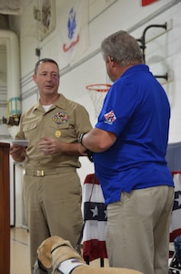 Master Chief Petty Officer Robert Bostic, Naval Consolidated Brig Charleston command master chief, presents a check on behalf of the NCBC Senior Enlisted Association, in the amount of $750, to Rick Hairston, Canines for Service president, June 19, 2014, at the NCBC on Joint Base Charleston, S.C. (U.S. Air Force photo/Eric Sesit)