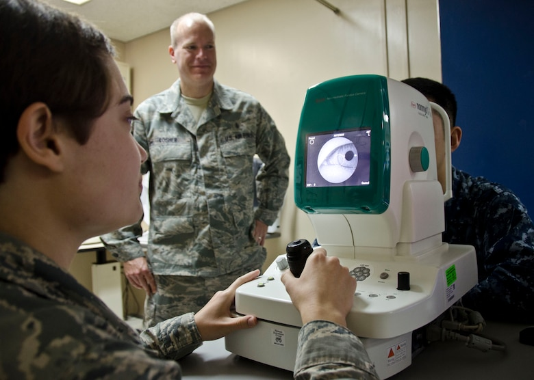 Airman 1st Class Jessica Borrowman, an optometry technician with the 126th Medical Group, trains with a fundus camera, used to take photos of a patient's retina, with optometry technician Tech. Sgt. Arthur Losher. June 12, 2014. Tech. Sgt. Losher and Airman Borrowman are members of the Illinois Air National Guard from Scott Air Force Base and are performing their two weeks of annual training by assisting at the Branch Health Clinic, Naval Air Facility Atsugi, Japan. (Air National Guard photo by Senior Airman Laura Muehl)