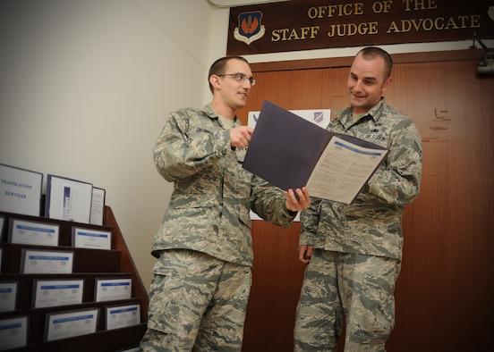 1st Lt. Jeremy Grunert, 39th Air Base Wing Legal Office chief of legal assistance, shows Staff Sgt. James Dorris, 39th ABW Legal Office NCO in charge of general law, legal references available to Airmen seeking legal guidance June 19, 2014, Incirlik Air Base, Turkey. Legal references can be found in front of the legal office located at the wing headquarters building. Judge advocates offer in-person legal assistance, and also offer a variety of resources to help the servicemen and women address their legal concerns. (U.S. Air Force photo by Staff Sgt. Veronica Pierce/Released)