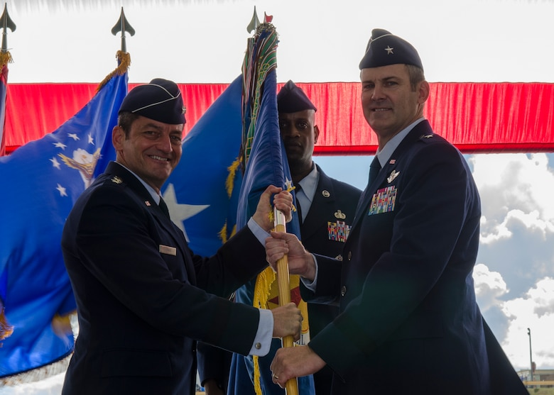 Lt. Gen. Russell Handy (left), 11th Air Force commander, passes the 36th Wing guidon to Brig. Gen. Andrew Toth during the Wing change of command ceremony June 19, 2014, on Andersen Air Force Base, Guam.  The unit guidon serves to identify the unit and is a symbol of the commander's authority and presence. (U.S. Air Force photo by Senior Airman Katrina M. Brisbin/Released)
