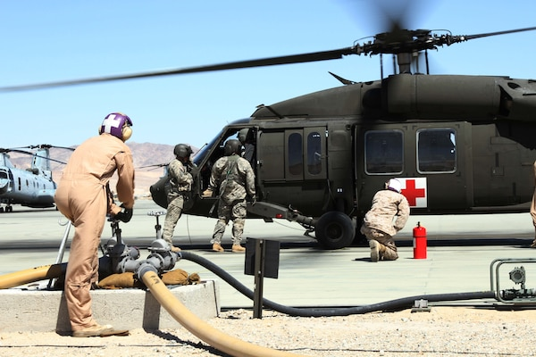 Marines at Twenty Nine Palms refuel a New Mexico National Guard helicopter during joint training.