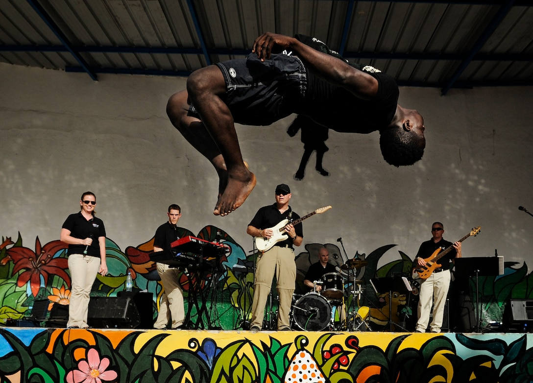 "The U.S. Air Forces in Europe and Air Forces Africa rock band, ""Afterburner"", performs for more than 60 children while gymnasts fly through the air during a concert at an orphanage June 18, 2014, in Dakar, Senegal. USAFE-AFAFRICA Airmen are in Senegal for the African Partnership Flight, a program designed to improve communication and interoperability between regional partners in Africa. The band will be playing multiple venues in the area to inspire children and musicians through the universal language of music. (U.S. Air Force photo/Staff Sgt. Ryan Crane)"