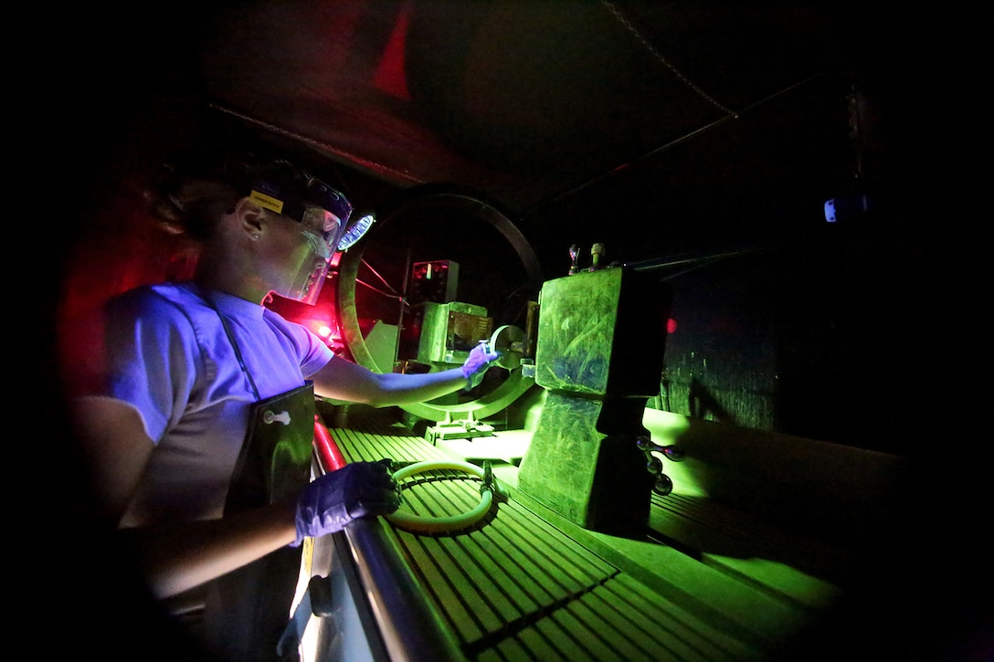 Airman 1st Class Amy Ferry looks over a piece of training metal during a magnetic particle inspection June 18, 2014, on Atlantic City Air National Guard Base, N.J. A magnetic particle inspection reveals any surface and subsurface defects of magnetic metal items. Ferry is a nondestructive inspection specialist assigned to the New Jersey Air National Guard's 177th Aircraft Maintenance Squadron. (U.S. Air National Guard photo/Tech. Sgt. Matt Hecht)