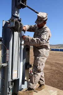 Corporal Allan Lopatinsky, a water support technician with I Marine Expeditionary Force Headquarters Group, adjusts a light during the 2014 I Marine Expeditionary Brigade command post exercise aboard Camp Pendleton, Calif., June 19, 2014. The CPX was designed to help improve the 1st Marine Expeditionary Brigade's readiness for deployment. (U.S. Marine Corps photo by Lance Cpl. David Silvano/released)