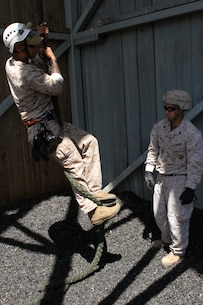 Marines with 2nd Battalion, 4th Marine Regiment and 2nd Battalion, 7th Marine Regiment, are instructed on fast-roping during the Helicopter Rope Suspension Techniques course aboard Camp Pendleton, Calif., June 16, 2014. This was a 13-day course which began June 11, where the Marines learned how to tie knots, and fast rope and rappel from towers and helicopters. (U.S. Marine Corps photo by Lance Cpl. Tony Simmons)