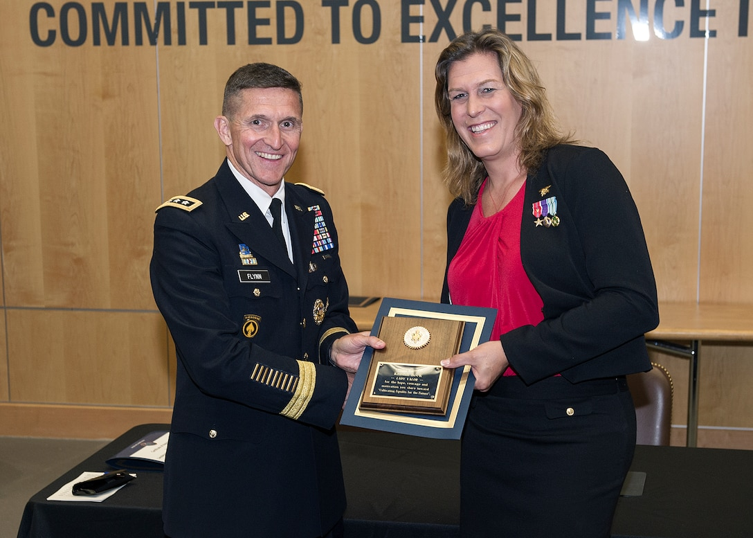 Retired Navy SEAL Kristin Beck receives a plaque from DIA Director Lt. Gen. Michael Flynn following the agency's Pride Month event June 18.