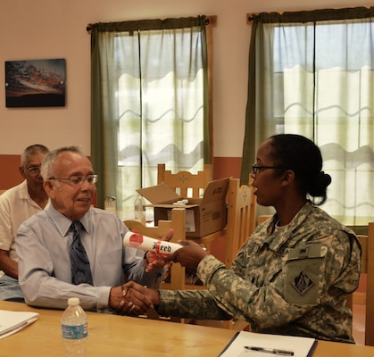 COCHITI PUEBLO, N.M., -- Albuquerque District Commander Lt. Col. Antoinette Gant relinquishes land acquired by the Corps during the construction of Cochiti Dam over 50 years ago to Cochiti Governor Joseph Suina, June 5, 2014.
