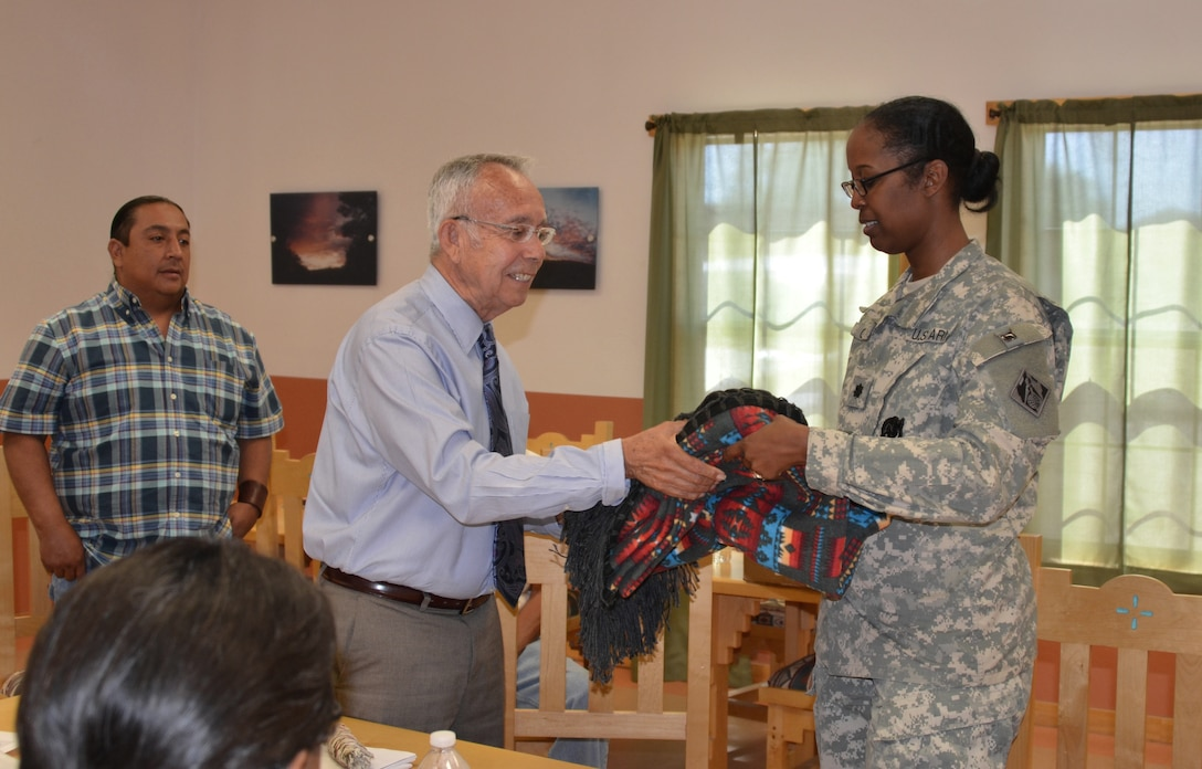 COCHITI PUEBLO, N.M., -- Cochiti Governor Joseph Suina presents Lt. Col. Gant with a blanket made by the family of one of the Tribal Council members. The June 5, 2014, Corps-Cochiti partnership meeting is the final one for Gant, who is departing the District June 26 for her next position at the Pentagon.