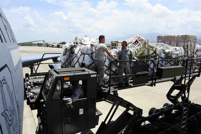 Two U. S. Air Force servicemembers from the 612th Air Base Squadron, Joint Task Force-Bravo, Soto Cano Air Base, Honduras, unload over 29,000 pounds of humanitarian aid and supplies from a U. S. Air Force KC-10 Extender bound for Honduran citizens in need June 6, 2014.  The supplies were sent to Honduras through the Denton Program, which allows private U.S. citizens and organizations to use space available on U.S. military cargo planes to transport humanitarian goods to approved countries in need.  (Photo by Martin Chahin)