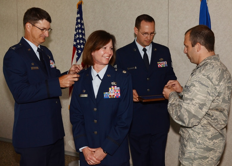 During a ceremony held at Whiteman AFB, June 10, 2014, Col. Kimbra Sterr's new silver eagles are pinned on by her spouse, Lt. Col Chad Sterr, and 131st Bomb Wing Missouri Air National Guard wing commander, Col. Mike Francis. Sterr is the 131st Maintenance Group commander.   (U.S. Air National Guard photo by Senior Master Sgt. Mary-Dale Amison)