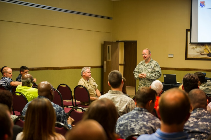 Col. Jeffrey DeVore, Joint Base Charleston commander, discusses base topics with the crowd at a commander's call, June 19, 2014, at Joint Base Charleston, S.C. Base leadership answered questions from the audience and talked about the future of JB Charleston. (U.S. Air Force photo/Senior Airman George Goslin)