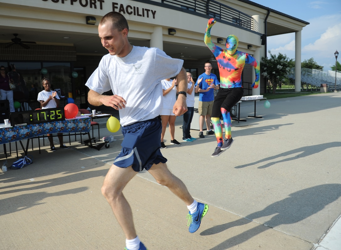 Airman 1st Class Paul Krukowski, 336th Training Squadron, finishes a 5K run with a time of 17 minutes 25 seconds as Airman Basic Peter Litman, 335th Training Squadron, cheers him on June 19, 2014, at the Triangle, Keesler Air Force Base, Miss.  The super hero themed event hosted by the 81st Training Group teal rope program raised more than $1,300 for the Gulf Coast Women's Shelter for Non-Violence.  (U.S. Air Force photo by Kemberly Groue)