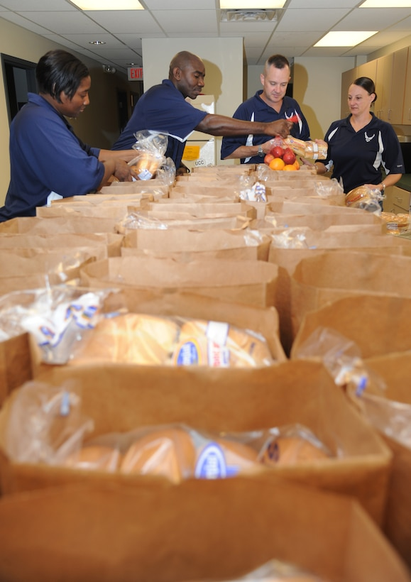"Senior Master Sgt. Lisbeth Farnum, 81st Aerospace Medicine Squadron, Master Sgt. Michael Davis, 81st Medical Operations Squadron, Master Sgt. Charles Sargent, 81st Medical Support Squadron, and Master Sgt. Laurie Holmes, 81st Training Wing, represent the Keesler Air Force Base Top III as they pack groceries into bags for families June 18, 2014, at Back Bay Mission in Biloxi, Miss.  The Top III raised more than $1,500 for the Back Bay Mission ""Summer Food Program"" which was used to purchase a one-week supply of food for 50 families. (U.S. Air Force photo by Kemberly Groue)"