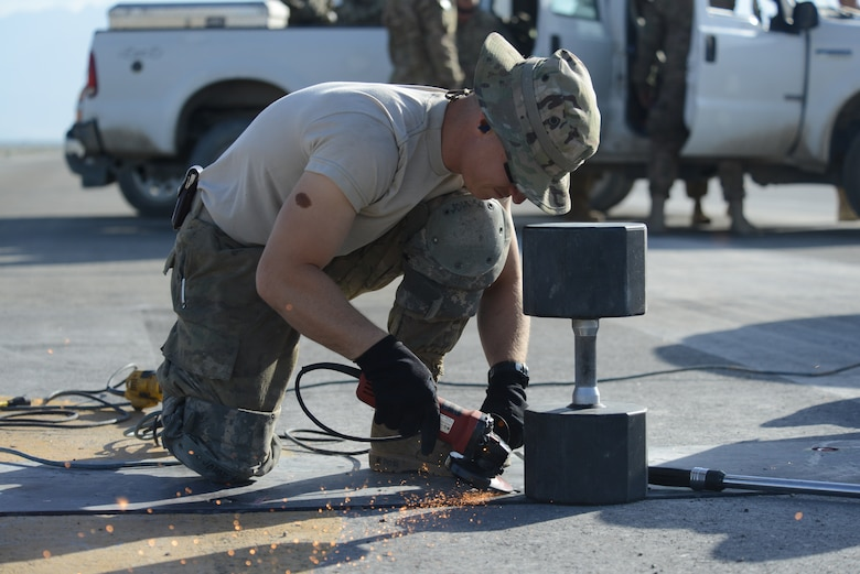 U.S. Air Force Tech. Sgt. James Johnson, a structures craftsman assigned to the 455th Expeditionary Civil Engineer Squadron grinds the top of a bolt securing a poly panel on the flight line of Bagram Airfield, Afghanistan June 8, 2014. Johnson grinds down the bolts to keep them from interfering with takeoff and landing procedures. More than 500 bolts out of 992 were replaced due to improper installatio procedures by a previous contractor. Johnson is deployed from the 142nd Air National Guard in Portland, Ore. (U.S. Air Force photo by Master Sgt. Cohen A. Young/Released)