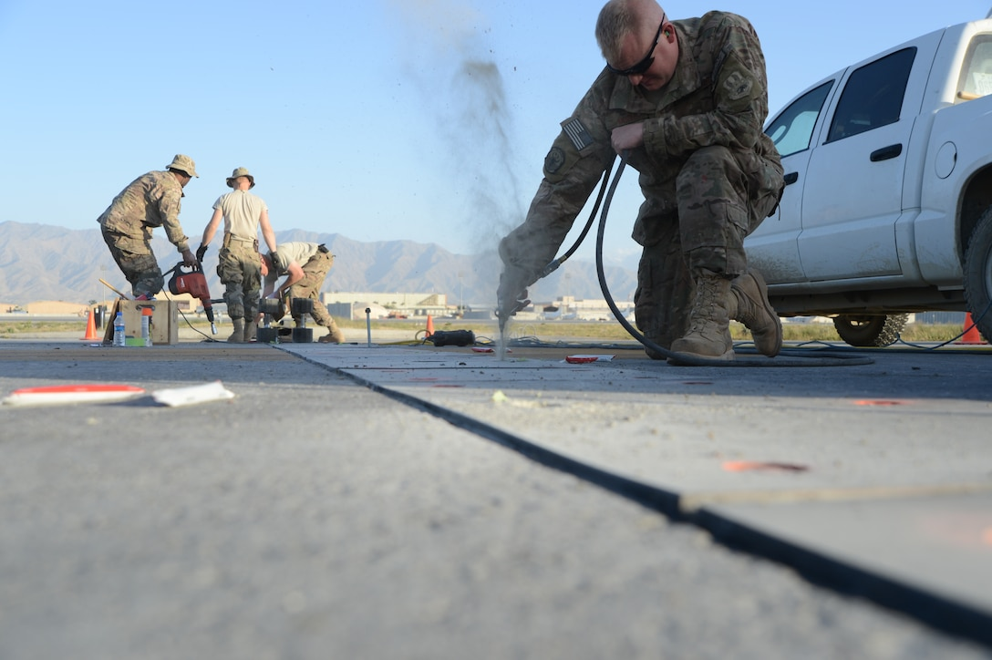 U.S. Air Force Tech. Sgt. C. J. White, a native of Houston, Texas and a heavy equipment operator assigned to the 455th Expeditionary Civil Engineer Squadron clears out dusts and rocks in a hole that will be used to install bolts in the ground to hold poly panels in place to secure aircraft arresting system cables at Bagram Airfield, Afghanistan June 8, 2014. Airmen replaced 502 bolts on the flight line. White is deployed from the 147th Reconnaissance Wing, Texas Air National Guard, Ellington Field Joint Reserve Base, Houston, Texas. (U.S. Air Force photo by Master Sgt. Cohen A. Young/Released)