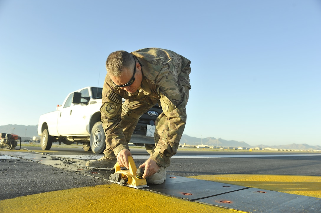 Senior Master Sgt. Douglas Ion, 455th Expeditionary Civil Engineer Squadron project non-commissioned officer in charge, uses a power plainer to remove poly panel material to prevent potential aircraft mishaps on the flightline at Bagram Airfield, Afghanistan June 9th, 2014. Ion is a native of Duluth, Minnesota and is deployed from the Air National Guards' 148th Fighter Wing, Duluth, Minnesota. (U.S. Air Force photo by Airman 1st Class Bobby Cummings/Released)