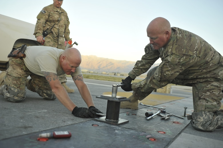 Master Sgt. Joshua Graves (left), 455th Expeditionary Civil Engineer Squadron superintendent, and Master Sgt. Jeremiah Graves, 455th ECES non-commissioned officer in charge of operations, conduct repairs on the main runway at Bagram Airfield, Afghanistan June 9th, 2014. Joshua and Jeremiah, two brothers from Duluth, Minnesota are deployed from the Air National guards' 148th Fighter Wing, Duluth, Minnesota. (U.S. Air Force photo by Airman 1st Class Bobby Cummings/Released)