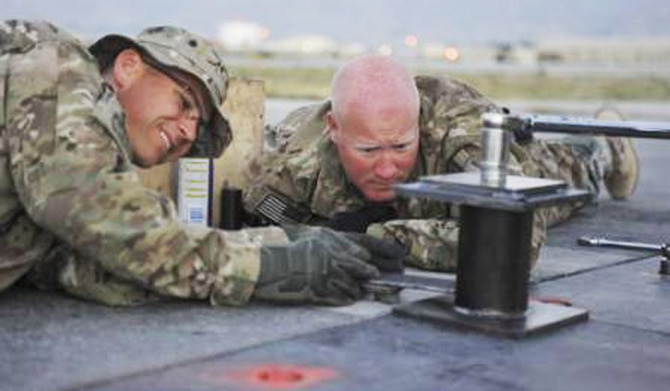 Maj. Ryan Kaspari (left) 455th Expeditionary Civil Engineer Squadron operations chief, and Master Sgt.  Jeremiah Graves, 455th ECES NCO in charge of operations, conduct repairs on the main runway at Bagram Airfield, Afghanistan June 9th, 2014. Kaspari and Graves are natives of Duluth, Minnesota and are deployed from the Air National guards' 148th Fighter Wing, Duluth, Minnesota. (U.S. Air Force photo by Airman 1st Class Bobby Cummings/Released)