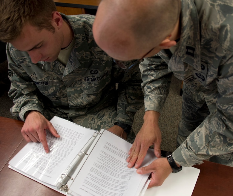 U.S. Air Force Capt. Allen Thill, right, assists Senior Airman Timothy Wigton with finding information in an Air Force Instruction manual in Little Falls, Minn., June 12, 2014. Wigton is in the last phase of his upgrade skill training during which he was evaluated on his knowledge of weather. 