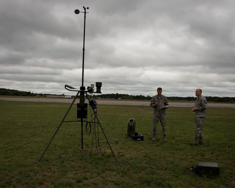 U.S. Air Force Master Sgt. James Emery, right, and Senior Airman Timothy Wigton, both from the 208th Weather Flight, collect weather information in Little Falls, Minn., June 12, 2014. Emery and Wigton participated in a training exercise with the Minnesota Army National Guard, Charlie Company, 834th Aviation Support Battalion where they provide up to date weather conditions for the pilots. 