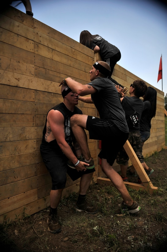 Airman 1st Class Kyle Harvey, 51st Comptroller Squadron, gives Airman 1st Class Zeke Garschagen, 51st Fighter Wing Judge Advocate military justice paralegal, a leg up over an 8-foot wall during a Spartan Race in Seoul, Republic of Korea, June 15, 2014. The walls ranged from 4 to –8 feet high. (U.S. Air Force photo/Senior Airman David Owsianka)