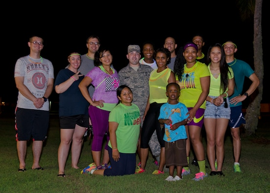 Lesbian, Gay, Bisexual and Transgender Pride Month committee members stand with volunteers after a glow run June 18, 2014, on Andersen Air Force Base, Guam. President Obama issued a proclamation this month recognizing the contributions LGBT Americans make to the Department of Defense. (U.S. Air Force photo by Senior Airman Katrina M. Brisbin/Released)