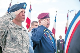 "First Inf. Div. Command Sgt. Maj. Michael A. Grinston and retired Command Sgt. Maj. Bill Ryan, a former 1st Inf. Div. Soldier, salute during Taps on June 5 during a ceremony at the ""Big Red One"" monument at Omaha Beach in Normandy, France. Ryan was wounded as he approached the beach during the D-Day invasion on June 6, 1944."