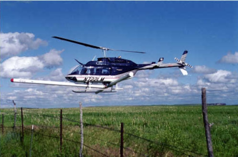 The helicopter in this image is flying an EM/Magnetometer system at a 2-meter altitude to characterize metal distribution over a former impact area.