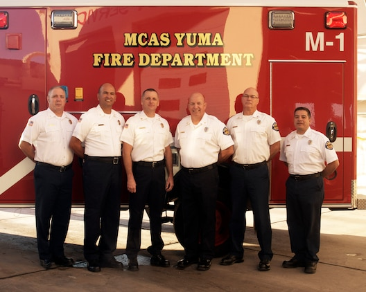 The Marine Corps Air Station Yuma, Ariz., fire department celebrated their achievement as the DoD Fire Prevention Program of the Year for 2013 after competing against other Marine Corps installations, May 14. The staff, (from left to right) Fire Inspectors James Taylor and Ricardo Pastrana, Fire Chief Michael Batson, Assistant Fire Chief J.C. Summers, Fire Inspectors Jeff Kindler and Greg Lopez, pose for a photo in front of their emergency vehicle, Jan. 13. Photo by: Lance Cpl. Summer Dowding