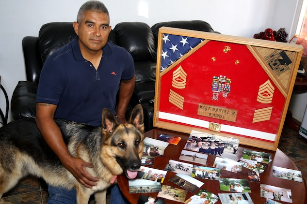 Retired Master Sgt. Daniel Ramos, with his dog Top, displays the shadow box he received upon his retirement from the Marine Corps and photos from various times and places during his career.  Ramos was a combat engineer and the first member of his family to join the armed services.  His son Daniel Ramos Jr. recieved his commission into the Navy May 23, 2014.