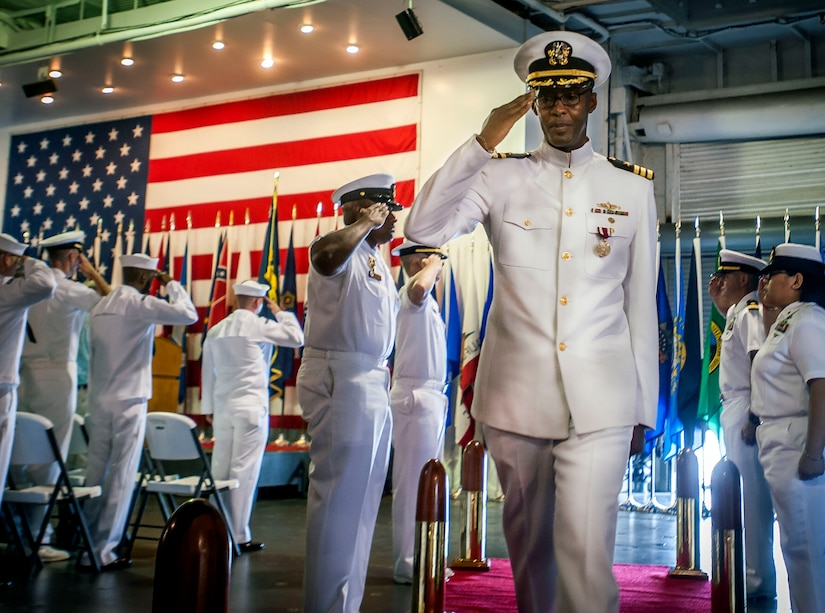 Commander Marquis Patton salutes the side boys as he is piped ashore during his retirement ceremony June 20, 2014, onboard USS Yorktown (CV 10) in Mount Pleasant, SC. Patton served 35 years in the U.S. Navy, beginning his career in 1979 as an enlisted seaman and being selected to chief petty officer before being commissioned and making his way through the officer ranks before retiring as a commander. (U.S. Air Force Photo/Senior Airman Tom Brading)