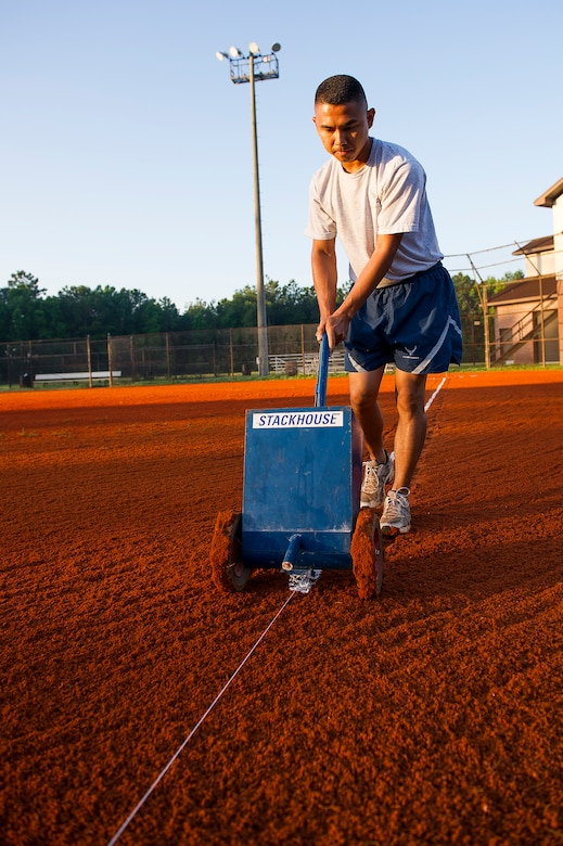 Staff Sgt. Lakan Ello, 628th Force Support Squadron fitness specialist, uses a chalk dispenser to put down a boundary line June 18, 2014, at Joint Base Charleston, S.C. New chalk lines are put down every game day to keep the field maintained for the players. (U.S. Air Force photo/Senior Airman George Goslin)