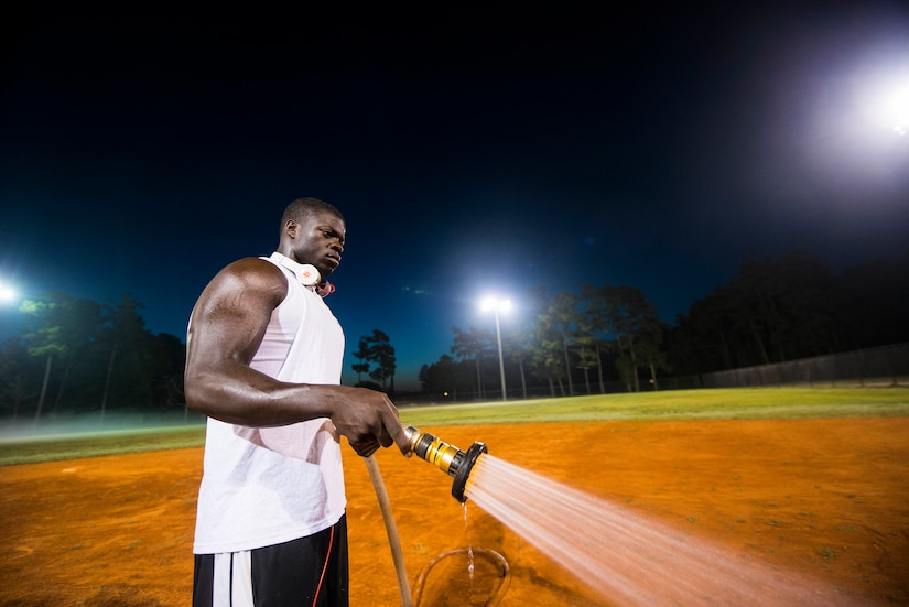 Staff Sgt. David Johnson, 628th Force Support Squadron sports program director, waters an infield, June 18, 2014, at Joint Base Charleston, S.C. The fields are watered to soften them up to give players more traction and prevent injury. (U.S. Air Force photo/Senior Airman George Goslin)