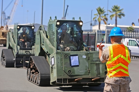 An embarkation specialist with Combat Logistics Battalion 15, Combat Logistics Regiment 15, 1st Marine Logistics Group, guides a pair of Multi-Terrain Loader Vehicles transporting a power generator to amphibious transport dock ship USS New Orleans (LPD-18) during an embarkation operation in support of a Defense Support of Civil Authorities training exercise aboard Naval Base San Diego, Calif., June 18, 2014. During DSCA operations, the Navy-Marine Corps team can provide local authorities with timely support, allowing them to send aid to areas in the United States where the infrastructure might be damaged beyond the local authorities' capabilities.