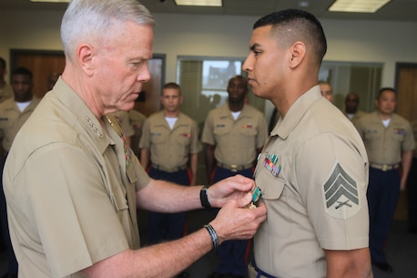 Sgt. Jose Flores, recruiter at Recruiting Substation Patchogue, receives a Navy and Marine Corps Achievement Medal from Gen. James F. Amos, Commandant of the Marine Corps, during a visit to Recruiting Station New York June 13.