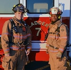 Senior Airman Boyd Korb, a 20th Civil Engineer Squadron firefighter, left, and Tech. Sgt. Joseph Charleston, the 20th CES station captain, stand in front of Ladder Truck 7 Dec. 18, 2013, on Shaw Air Force Base, S.C. Charleston and Korb received the Defense Department McAllister Outstanding Fire Department Team Award for Heroism April 9, 2013, for their actions directly related to saving the life of a civilian firefighter in Sumter, S.C. (Courtesy photo)