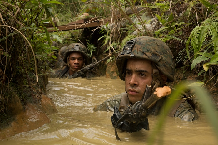 Cpl. Christian Hiraldo, right, leads his Marines and sailors through a mud pit during the jungle endurance course June 20 at the Jungle Warfare Training Center on Camp Gonsalves, Marine Corps Base Camp Smedley D. Butler, Marine Corps Installations Pacific. During the course, Marines and sailors were required to navigate the harsh jungle environment as well as man-made obstacles in the heat and humidity of Okinawa. Hiraldo is a Brooklyn, New York, native and rifleman with 1st Battalion, 8th Marine Regiment, which is currently assigned to 4th Marines, 3rd Marine Division, III Marine Expeditionary Force, under the unit deployment program.