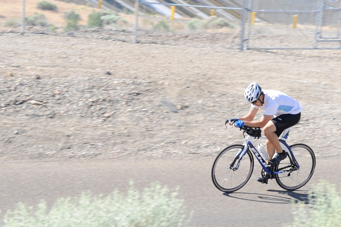 A participant rides toward the conclusion of the cycling portion of the 4th Annual iTri at Strike Dam, Idaho, June 21, 2014. In conjunction with cycling, participants also competed in swimming and running events. (U.S. Air Force photo by Senior Airman Caitlin Guinazu/Released)
